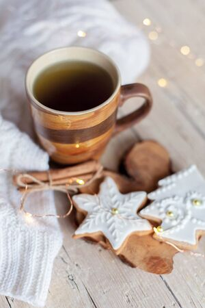 Christmas tea time. Mug of hot beverage, gingerbread cookies at wooden and knitted background. Cozy morning breakfast with homemade sweets and cup. Winter food, drinks, new year lights. 写真素材 - 134763562