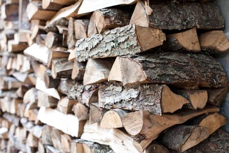 Woodpile of firewood by house. Chipped firewood laying. Preparation for winter. Close up. 写真素材