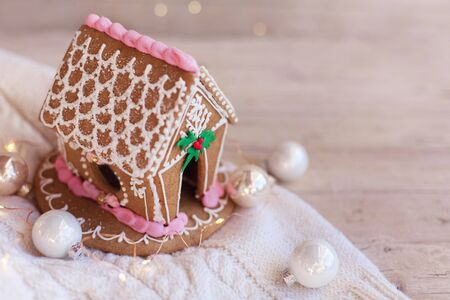 Gingerbread house, Christmas decorations on wooden and knitted background with glares. Homemade sweets is decorated with holly, new year lights, garland and cute white and pink ornaments.