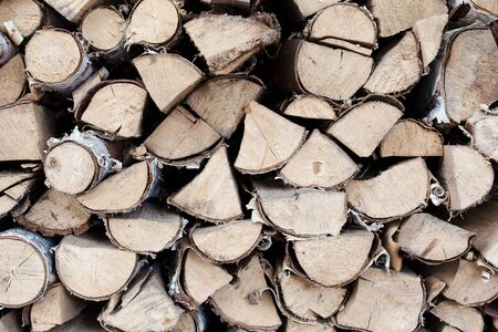 Firewood background. Preparation for winter. Pile of firewood in forest. Chipped firewood is on heap. Woodpile close up.