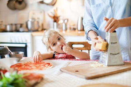 Funny kid gourmet is eating and tasting cheese. Family are cooking pizza in kitchen. Mother and daughter are preparing homemade italian food. Little girl is helping woman. Children chef concept. 写真素材