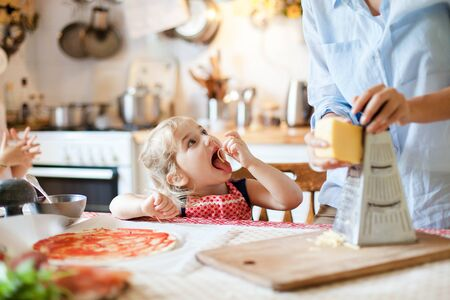 Family cooking pizza in kitchen. Mother and daughter preparing homemade italian food. Funny little girl gourmet is helping woman, eating and tasting cheese and ingredients. Children chef concept. 写真素材 - 134763571