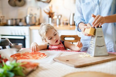 Family are cooking pizza in kitchen. Funny kid gourmet is eating and tasting cheese. Mother and daughter are preparing homemade italian food. Cute child is helping woman. Lifestyle, authentic moment. 写真素材