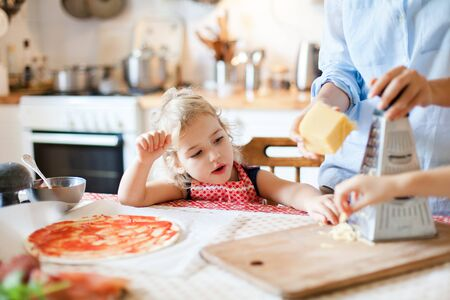 Funny child gourmet is eating and tasting cheese. Family are cooking pizza and preparing homemade italian food and meal in kitchen. Cute kid is helping mother. Lifestyle, authentic moment.