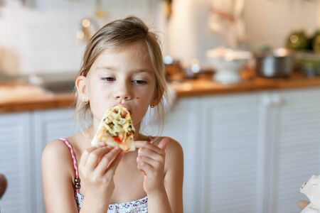 Kid girl is enjoying italian homemade pizza. Child is eating and tasting delicious food in cozy home kitchen. Lifestyle moment. 写真素材 - 134763883