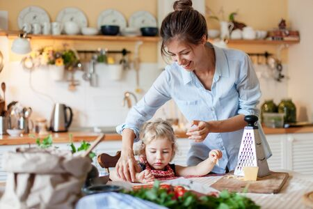 Family are cooking italian pizza in cozy home kitchen. Happy mother is teaching cute kid to prepare food or meal for Thanksgiving dinner. Little girl is helping woman. Children chef concept. 写真素材 - 134763884