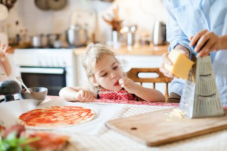 Funny Little girl gourmet is eating and tasting cheese. Family are cooking pizza in kitchen. Mother and daughter are preparing homemade italian food. Kid is helping woman. Children chef concept.