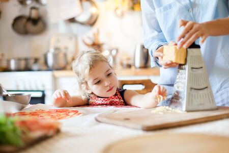 Funny kid gourmet is eating and tasting cheese. Family are cooking pizza and preparing homemade italian food and meal in kitchen. Cute little girl is helping mother. Children chief-cooker concept. 写真素材 - 134763924
