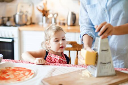 Family are cooking homemade pizza. Funny curious child is interested in preparing italian food and meal in cozy kitchen. Cute kid is helping mother to grate cheese. Lifestyle, authentic, candid moment 写真素材