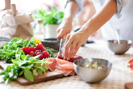 Woman is cooking in home kitchen. Female hands cut salami, vegetables, greens, tomatoes on table on wooden boards. Ingredients for preparing italian or french food. Lifestyle moment. 写真素材 - 134763927