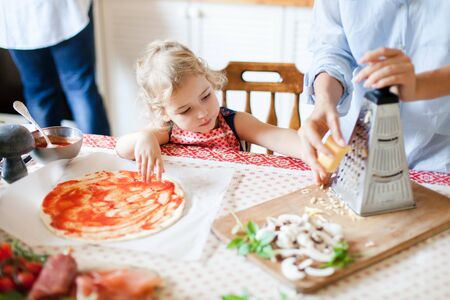 Family is cooking homemade pizza. Cute kid is helping mother to grate cheese. Funny curious child is interested in preparing italian food and meal in cozy kitchen. Lifestyle, authentic, candid moment 写真素材