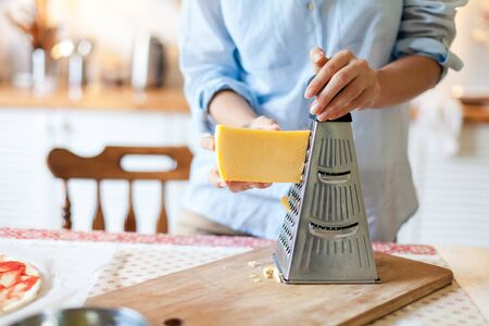 Woman grates cheese with grinder. Family is cooking pizza and homemade italian food in kitchen. Lifestyle moment. 写真素材 - 134763934
