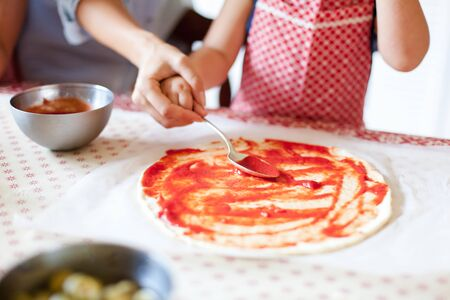 Family is cooking italian pizza in home kitchen. Mother is teaching kid to prepare food for dinner. Little girl is helping to smear ketchup with spoon. Children chef concept. Lifestyle, candid moment 写真素材 - 134763935
