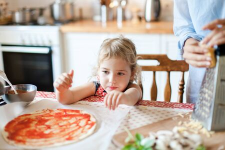 Funny curious child is helping mother. Family are cooking pizza and preparing homemade italian food and meal in kitchen. Cute little girl is sitting at table. Lifestyle, authentic, candid moment.