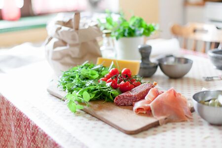 Kitchen table with ingredients for preparing pizza. Cooking process at home. Vegetables, cheese, greens, salami, tomatoes are on wooden boards.