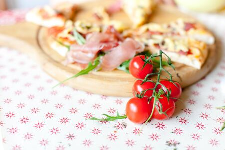 Pizza on wooden board. Cherry tomatoes and appetizing italian food on table. Close up. 写真素材