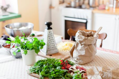 Kitchen table with ingredients for preparing pizza. Cooking process at cozy home. Vegetables, cheese, greens, dough, kraft paper bag with flour are on wooden boards. Using oven. 写真素材 - 134763941
