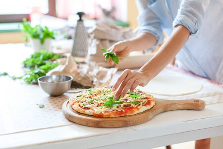 Woman is cooking pizza in cozy home kitchen. Female hands are decorating italian dinner with greens, fresh basil, arugula. Homemade pizza is served on wooden board on table. Lifestyle moment. Close up