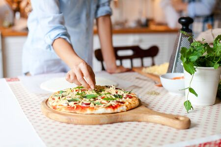 Woman is cooking pizza in cozy home kitchen. Girl is decorating italian dinner with greens, fresh basil, arugula. Homemade pizza is served on wooden board on table. Lifestyle moment. Close up.