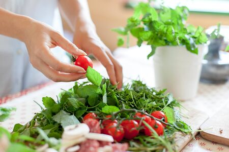 Woman is cooking in home kitchen. Female hands choose cherry tomatoes, vegetables for recipe. Ingredients for preparing italian or french food are on table on wooden boards. Lifestyle moment. Close up