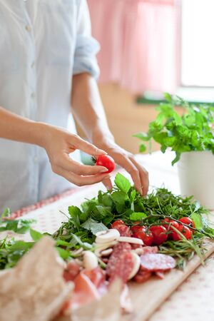 Woman is cooking in home kitchen. Female graceful hands hold cherry tomatoes. Ingredients for preparing italian or french food are on table on wooden boards. Lifestyle moment. Close up.