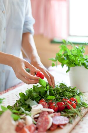 Woman is cooking in home kitchen. Female hands choose cherry tomatoes and vegetables. Ingredients for preparing italian or french food are on table on wooden boards. Lifestyle moment. Close up. 写真素材 - 134763947
