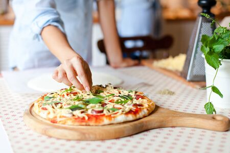 Woman is cooking pizza in cozy home kitchen. Female hands are decorating italian meal with greens, fresh basil, arugula. Homemade pizza is served on wooden board on table. Lifestyle moment. Close up