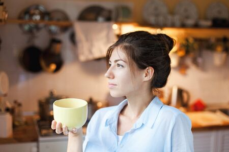 Young woman is drinking tea in cozy home kitchen. Happy girl is enjoying and holding mug of coffee. Housewife has tea break in cooking.