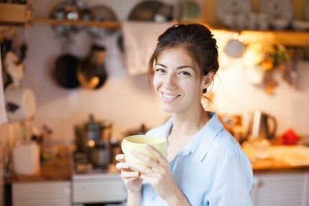 Young woman is drinking tea in cozy home kitchen. Happy girl is enjoying break in cooking and holding mug of coffee.