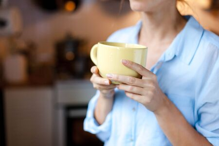 Graceful female hands hold mug of tea. Young woman is drinking coffee in cozy home kitchen. Close up. 写真素材 - 134763951