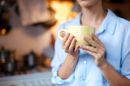 Graceful female hands hold cup of tea. Young woman is drinking coffee in cozy home kitchen. Close up.