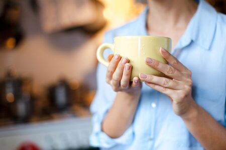 Graceful female hands hold cup of coffee. Young woman is drinking tea in cozy home kitchen. Close up. Zdjęcie Seryjne