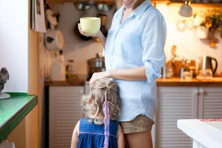 Mother comforts daughter in cozy kitchen. Woman is drinking tea. Child girl needs attention. Mom is hugging kid. Concept of kindness, care, family support, motherhood. Maternity lifestyle moments. 写真素材 - 134763956