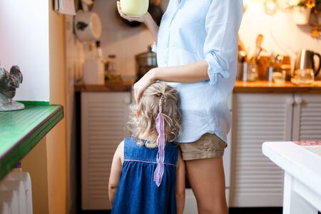 Mother is hugging kid. Mom comforts daughter in cozy kitchen. Woman is drinking tea. Child girl needs attention. Concept of kindness, care, family support, motherhood. Maternity lifestyle moments. 写真素材 - 134763957