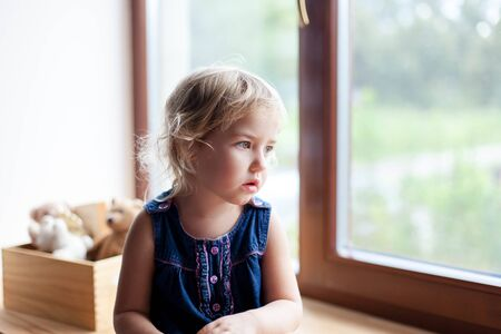 Sad child is sitting on window sill. Cute kid is looking through window. Little girl is worry, bored. Lifestyle, authentic, candid moment. 写真素材 - 134763963