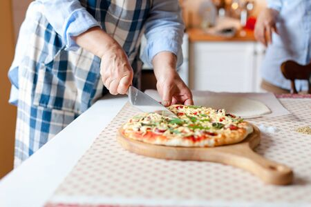 Woman cuts hot pizza on wooden board in cozy home kitchen. Cooking process of italian family dinner at home. Lifestyle moment. Close up of female hands with knife. 写真素材