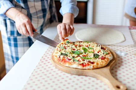 Woman cuts hot pizza on wooden board in cozy home kitchen. Cooking process of italian family dinner at home. Female hands hold knife and slice of pizza. Lifestyle moment. 写真素材