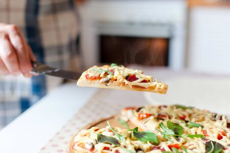 Woman holds steamy slice of hot pizza in cozy home kitchen. Cooking process of italian family dinner at home. Lifestyle and real moment. 写真素材 - 134763968