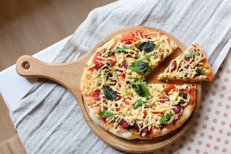 Homemade italian pizza and slice with parmesan cheese, fresh basil, arugula, tomatoes served on wooden board on kitchen table. Top view, rustic background.