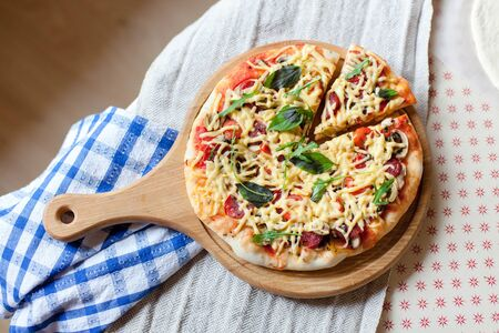 Homemade italian pizza and slice with parmesan cheese, fresh basil, arugula, tomatoes served on wooden board on kitchen table. Flat lay, rustic background. 写真素材 - 134763972