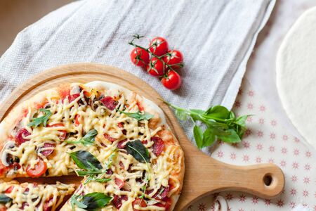 Homemade italian pizza, fresh cherry tomatoes and basil, arugula served on wooden board on kitchen table. Top view, rustic background. 写真素材 - 134763973