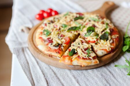 Homemade italian pizza, fresh cherry tomatoes and basil, arugula served on wooden board on kitchen table with linen towel. 写真素材 - 134763974