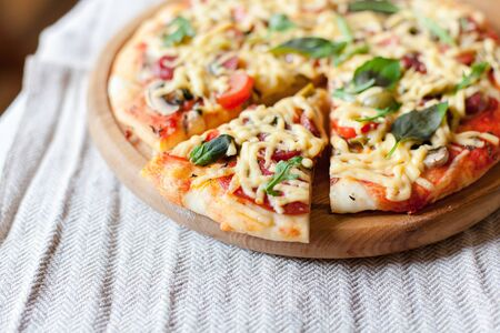 Homemade italian pizza with slice served on wooden board on kitchen table with linen towel. Close up. 写真素材 - 134763975