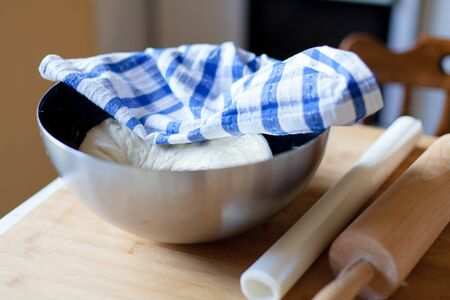 Yeast cookie dough in metal bowl covered with checkered blue towel. Rolling pin, baking paper preparing for cooking on home kitchen table.