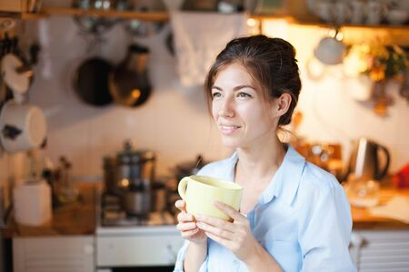 Young woman is drinking tea in cozy home kitchen. Happy girl is smiling and holding mug of coffee. Housewife has tea break in cooking.