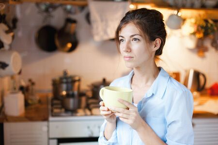 Young woman is drinking tea in cozy home kitchen. Happy girl is smiling and holding mug of coffee. Housewife has tea break in cooking. 写真素材 - 134763978