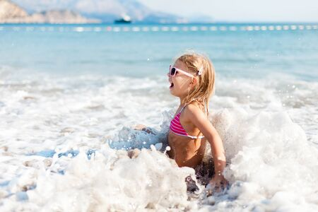 Kid is swimming in waves at sea beach in vacation. Child girl is enjoying summer holiday. Concept of travel, family fun and water safety. Lifestyle, authentic candid moments, emotions. 写真素材 - 135180672