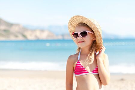 Beach girl in summer vacation. Kid at sea coast. Holiday, travel and summertime concept. Child in straw hat and sunglasses is happy tourist in resort outdoors. Cute lady is smiling, enjoying party. 写真素材 - 135180639