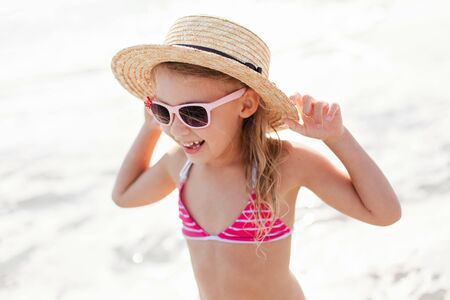Funny kid at sea beach in summer vacation. Child girl in straw hat and sunglasses is smiling, laughing. Concept of holiday, travel, happiness and enjoying life. Lifestyle, authentic moments, emotions. 写真素材