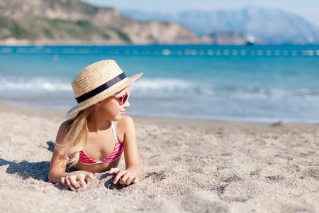 Kid is lying on sandy sea beach in summer vacation. Holiday, travel and summertime concept. Cute girl in straw hat and sunglasses is happy tourist in resort outdoors. Child is wellbeing, enjoying sun.